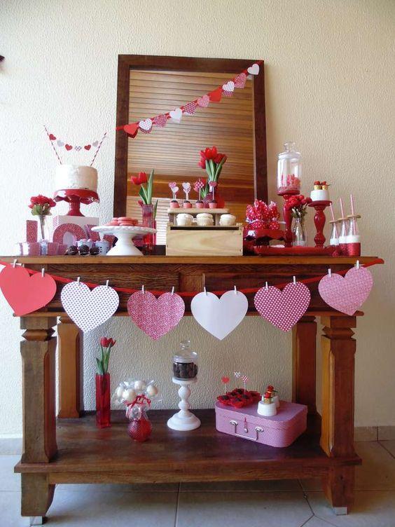 Guirnaldas de corazones, siluetas y recortes más algunas flores y dulces  inspirados en San Valentín son una buena decoración para la ocasión.