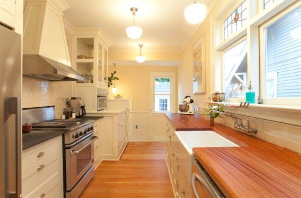 en esta cocina se han combinado varios tipos de encimera es otra posibilidad pero hay que destacar el bonito efecto de la encimera de madera con el suelo