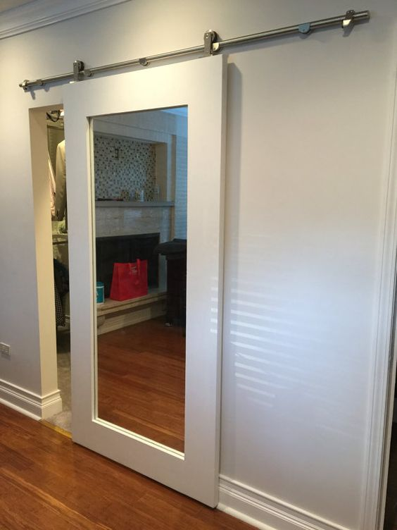 Ten un armario con puertas de espejo for Perchas para puertas sin agujeros