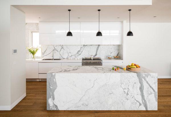 muebles en blanco y frente de cocina e isla en mrmol blanco veteado de gris el suelo aporta ese contraste tan necesario en cualquier decoracin