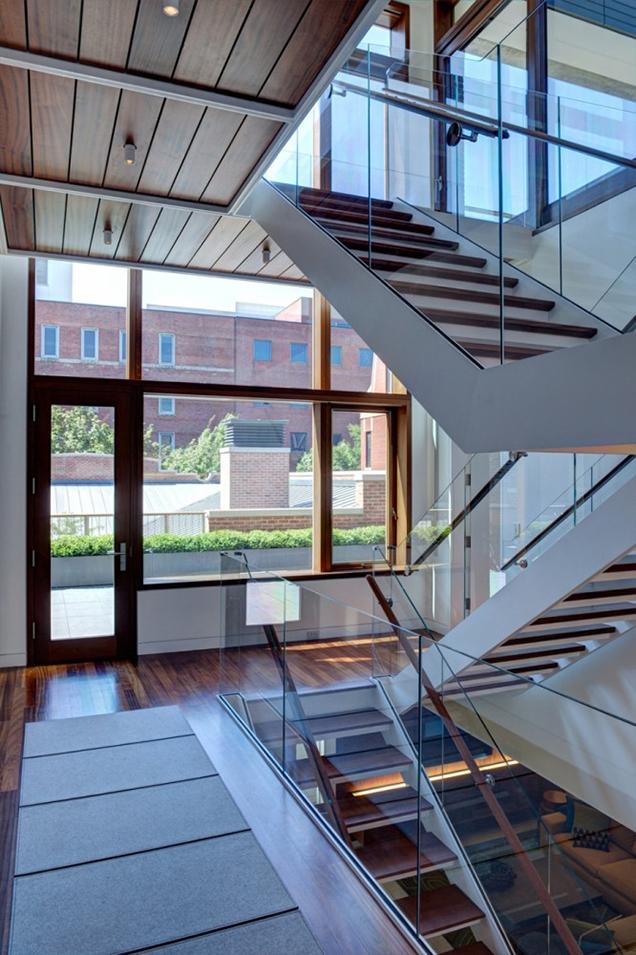 la elegancia escultrica de las escaleras modernas se ve enormemente destacada usando paneles de vidrio como barandilla