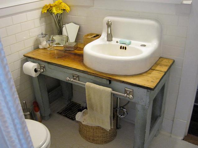 una vieja mesa de madera y un lavabo de porcelana reciclado conforman este bonito mueble de bao que se complementa con un portarollos y un toallero a juego - Lavabos Originales